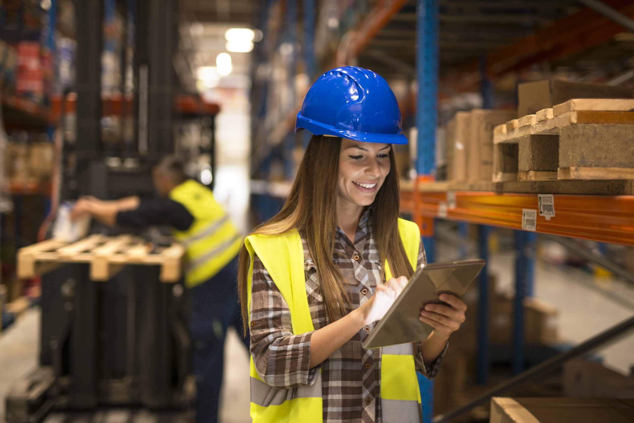 Female warehouse worker holding tablet checking inventory in distribution warehouse. Forklift in background.